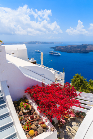 A view of caldera and typical red flowers on terrace of a house in Firostefani village, Santorini island, Greece