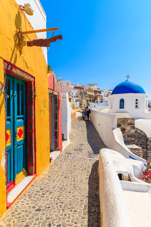 Narrow street with colourful house and church in Oia village, Santorini island, Greece