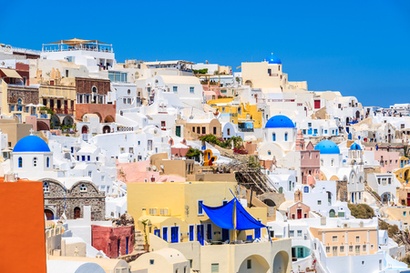 Colourful houses and churches with blue domes in Oia village on Santorini island, Greece