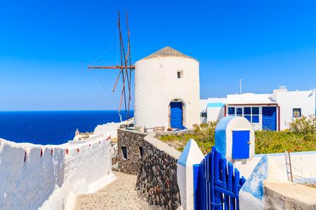 Typical white windmill on street of Oia village, Santorini island, Greece