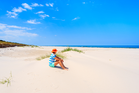 Young woman tourist sitting in sand on beautiful beach in Lubiatowo coastal village, Baltic Sea, Poland