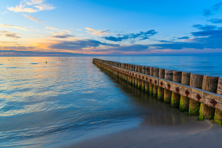 Sunset on beach with a wooden breakwater in Leba, Baltic Sea, Poland Stock Photo