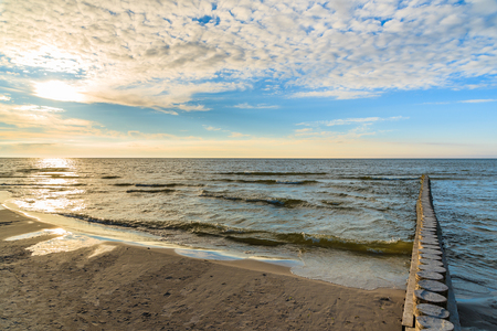 Wooden breakwaters on Leba beach during sunny day with clouds, Baltic Sea, Poland Stock Photo