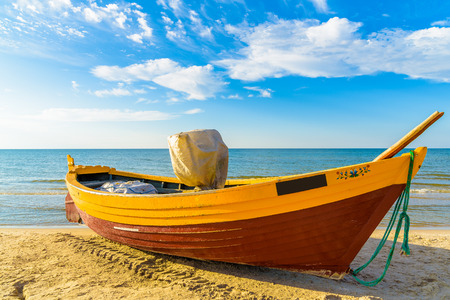 Typical fishing boat on a beach in Debki coastal village at sunset time, Baltic Sea, Poland