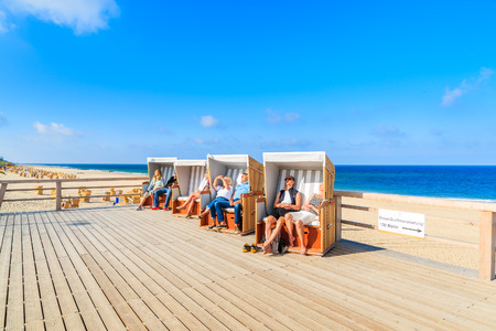 SYLT ISLAND, GERMANY - SEP 6, 2016: people sitting in wicker chairs on coastal promenade in Wenningstedt village. 報道画像