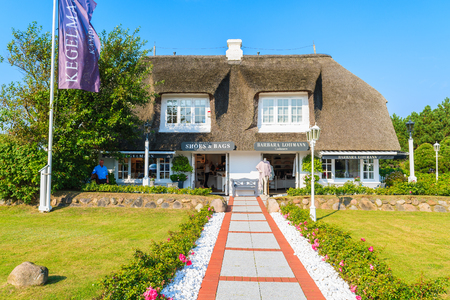 KAMPEN, SYLT ISLAND - SEP 7, 2016: path to luxury shop in Kampen village which is famous for its traditional thatched roof houses, Germany.