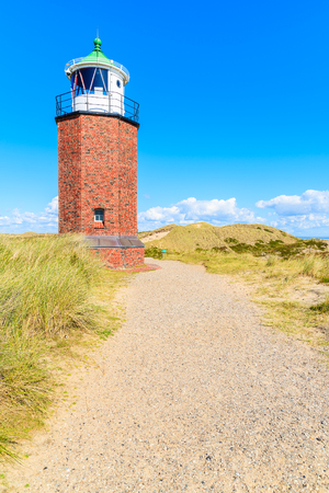 Lighthouse on sand dune against blue sky with white clouds on northern coast of Sylt island near Kampen village, Germany