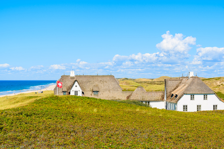 Typical Frisian houses with straw roofs on cliff at Kampen beach, Sylt island, Germany Editorial