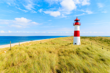 Ellenbogen lighthouse on sand dune against blue sky with white clouds on northern coast of Sylt island, Germany