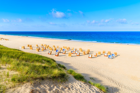 Grass on sand dune and wicker chairs on Wenningstedt beach, Sylt island, Germany Stock Photo