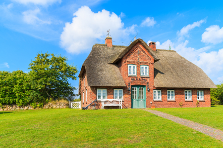 SYLT ISLAND, GERMANY - SEP 6, 2016: typical red brick Frisian house with thatched roof on Sylt island in List village, Germany. Redactioneel