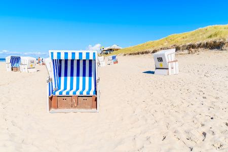 Wicker chairs on sandy beach in Kampen village, Sylt island, Germany