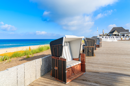 SYLT ISLAND, GERMANY - SEP 6, 2016: wicker chair and restaurant on coastal promenade in Wenningstedt village on Sylt island, Germany.