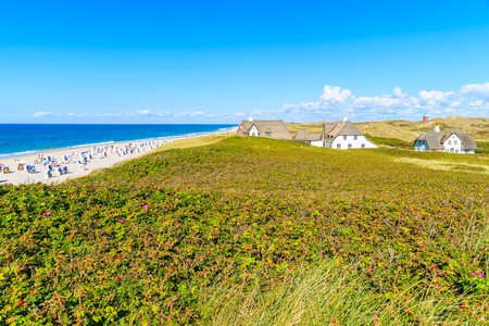 Typical Frisian houses with straw roofs on cliff at Kampen beach, Sylt island, Germany Stock Photo