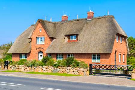 SYLT ISLAND, GERMANY - SEP 7, 2016: typical red brick house with thatched roof on street of Kampen village on Sylt island, Germany. Stockfoto