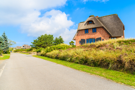 Road in Westerheide village with typical house on side, Sylt island, Germany Stock Photo