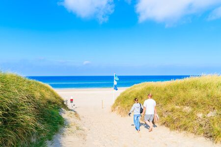 Unidentified couple of people walking to beach among grass sand dunes, Sylt island, Germany