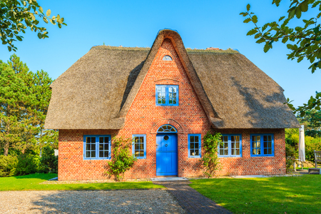 Traditional red brick house with thatched roof in Kampen village on Sylt island, Germany