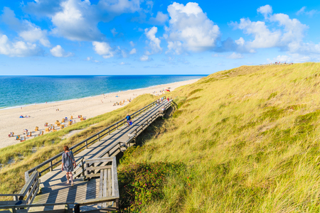 Woman tourist walking on wooden walkway along a coast of North Sea and view of beautiful beach near Wenningstedt village, Sylt island, Germany Stock Photo