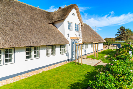 Traditional white house with thatched roof in Wenningstedt village on Sylt island, Germany
