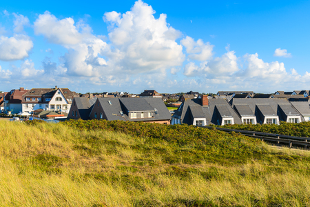 View of typical houses in Wenningstedt village with grass sand dune in foreground on Sylt island, Germany