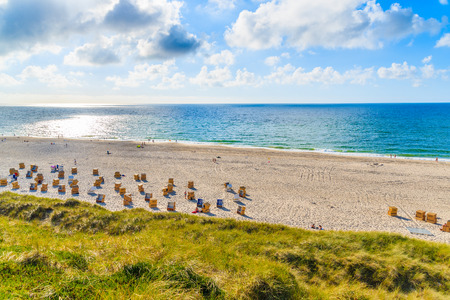 View of beach with wicker chairs against  sun on blue sky, Sylt island, Germany