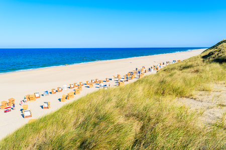 Grass on sand dune and view of white sand Kampen beach on Sylt island, Germany