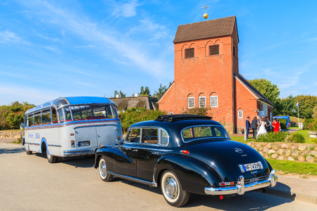SYLT ISLAND, GERMANY - SEP 10, 2016: classic black Mercedes Benz limousine and bus parking in front of a church in Wenningstedt village ready for transporting guests from wedding ceremony.