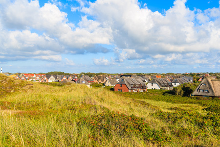 Sand dune with grass and houses of Wenningstedt village in background, Sylt island, Germany