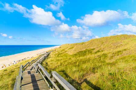 Wooden walkway along a coast of North Sea and view of beautiful beach near Wenningstedt village, Sylt island, Germany