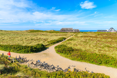 SYLT ISLAND, GERMANY - SEP 11, 2016: Bikes parked on coastal path in Kampen village on western coast of Sylt island, Germany.