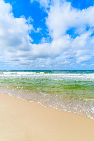 Sea waves on beautiful sandy beach on sunny summer day, Sylt island, Germany