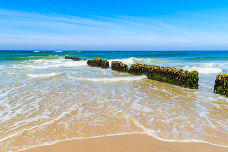 Breakwaters and sea waves on beautiful sandy beach on sunny summer day, Sylt island, Germany
