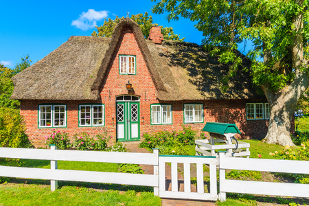Traditional red brick house with thatched roof in Keitum village on Sylt island, Germany