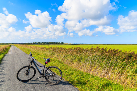 SYLT ISLAND, GERMANY - SEP 9, 2016: bike on road in green countryside landscape of Sylt island near Keitum village, Germany. Editorial