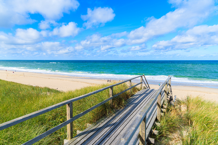 Wooden footbridge from sand dune to beautiful beach near Westerland village, Sylt island, Germany