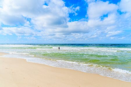Woman surfer in sea water at Kampen beach, North See, Sylt island, Germany Banque d'images
