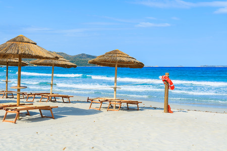 Sunbeds with umbrellas and lifesaver ring on white sand beach in Porto Giunco bay, Sardinia island, Italy