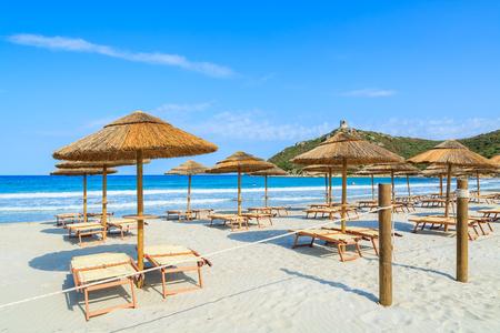 Entrance gate to white sand beach with sun chairs and umbrellas in Porto Giunco bay, Sardinia island, Italy