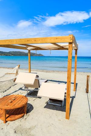 Sun chairs with wooden teak table on white sand beach in Porto Giunco bay, Sardinia island, Italy