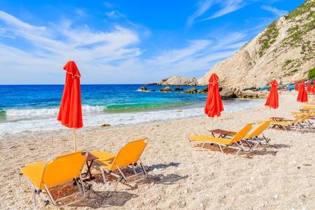 Yellow sunbeds with red umbrellas on beautiful Petani beach, Kefalonia island, Greece