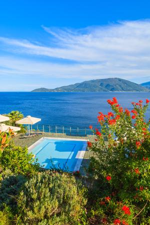 Swimming pool with sea and mountain view on coast of Kefalonia island in Agia Efimia village, Greece Stock Photo
