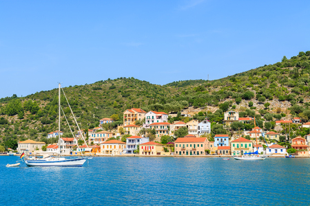 Yacht boat on sea with colourful houses of Vathi town in background, Ithaca island, Greece Banco de Imagens