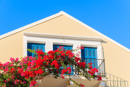 Red Bougainvillea flowers on balcony of typical Greek house in Fiskardo town, Kefalonia island, Greece Stock Photo