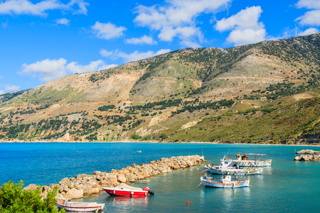 Typical Greek fishing boats in sea bay against mountains in Zola port, Kefalonia island, Greece Stock Photo