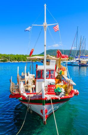 FISKARDO PORT, KEFALONIA ISLAND, GREECE - SEP 16, 2014: traditional greek fishing boat in port of Fiskardo village. Colourful boats are symbol of Greek islands.