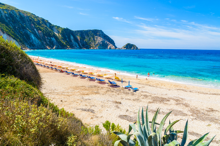 View of Petani beach with sunbeds and umbrellas and people swimming, Kefalonia island, Greece Stock Photo