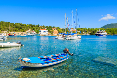 FISKARDO PORT, KEFALONIA ISLAND, GREECE - SEP 16, 2014: traditional Greek fishing boat in port of (No Suggestions) village. Colourful boats are symbol of Greek islands.