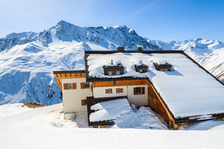 Mountain refuge hut covered with snow and peaks of Austrian Alps in background, Riffelsee ski resort in Pitztal valley 新聞圖片