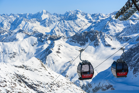 PITZTAL GLACIER, AUSTRIA - MAR 29, 2014: Gondola cable cars and ski slopes in the mountains of Pitztal winter resort, Austrian Alps.